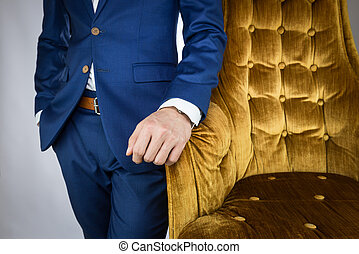 man in blue suit standing beside sofa