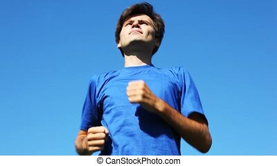 man in blue t-shirt runs on place before blue sky. type close from below