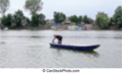 Man in boat - Blurred view on man in his boat on river.