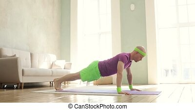 Man in bright sportswear is doing push-ups exercises on mat at home, side view.