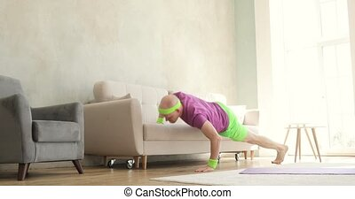 Man in bright sportswear is doing push-ups exercises using sofa at home.