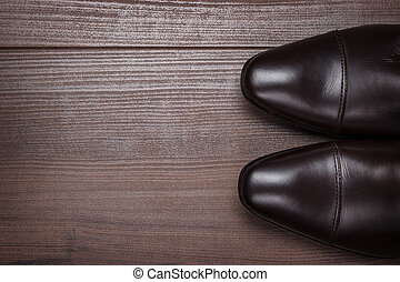 man in brown shoes standing on the wooden floor background
