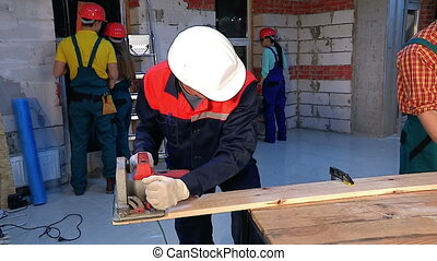 Man  in builder helmet and uniform with electric planer.