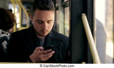 Man in bus using his cell phone. Reading emails. texting  message