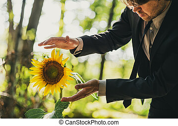Man in business suit holding his hands around sunflower