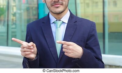 Man in business suit show gesture To the left outdoor