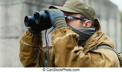 Man in camouflage looking through binoculars