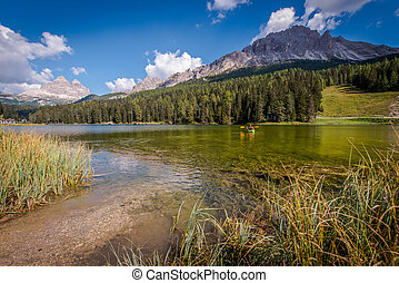 Man In Canoe Enjoying Summer On Italian Lake Misurina.