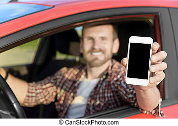 Man in car driving showing smart phone.