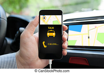 man in car holding phone with app taxi on screen