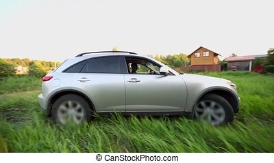 Man in car ride around by grass, at background of village