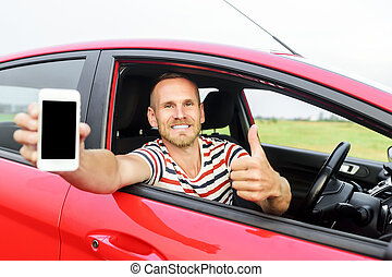 Man in car showing smart phone.
