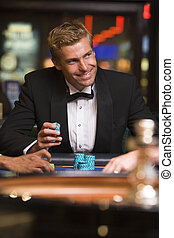 Man in casino playing roulette and smiling (selective focus)