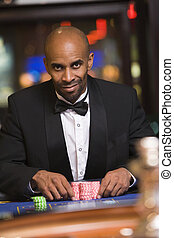 Man in casino playing roulette smiling (selective focus)