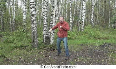 man in casual clothes does fighting martial arts on a forest...