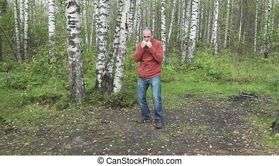 man in casual clothes does fighting martial arts on a forest glade,slow motion