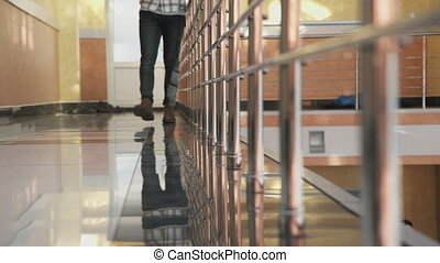 Man in casual clothes leisurely walks on the reflective floor.