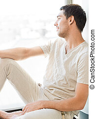 man in casual clothes sitting on the windowsill