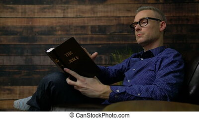 Man in chair reads Holy Bible