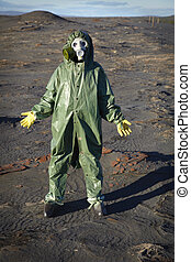 A man in a chemical protective suit stands in the desert