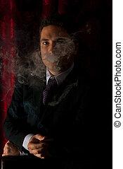 Man in cigar smoke in darkness