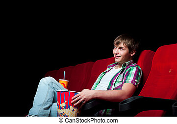 man in cinema - man in a movie theater, watching a movie and...