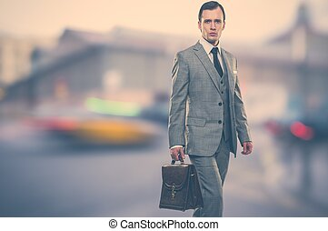 Man in classic grey suit with briefcase  outdoors