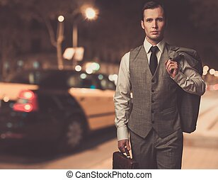 Man in classic grey suit with briefcase walking outdoors at night