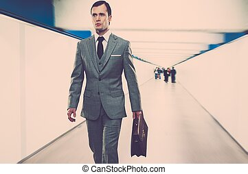 Man in classic grey suit with briefcase walking through corridor