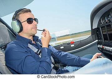 Man in cockpit of aircraft wearing headphones with microphone