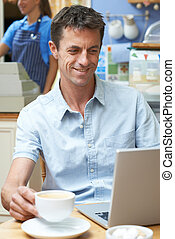 Man In Coffee Shop Using Laptop Computer