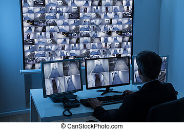 Man In Control Room Monitoring Cctv Footage - Rear View Of A...