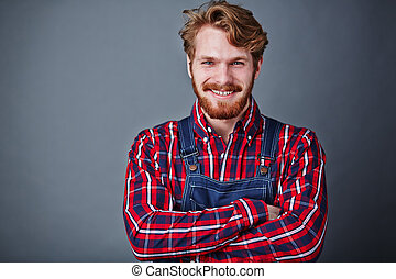 Man in coveralls - Handsome guy in coveralls looking at...