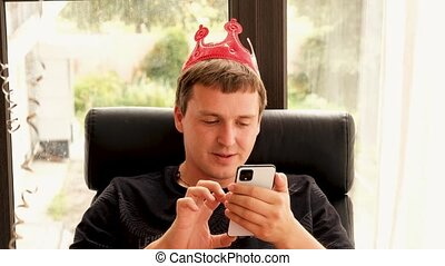 Man in crown using smartphone during birthday celebration - ...