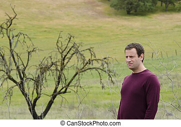 Man in deep thought outdoors in an open field.