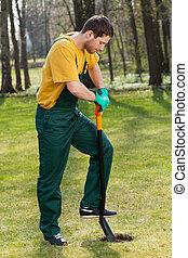 Man in dungarees digging in garden