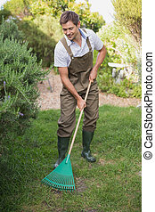 Full length of a young man in dungarees raking the garden
