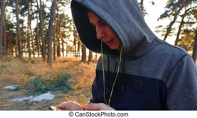 man in earphones is having rest and listening to music during listening to music on headphones on a smartphone running outdoors near modern private houses. man lifestyle running in the nature sports