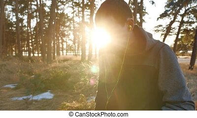 man in earphones is having rest and listening to music during listening to music on headphones on a smartphone running outdoors near modern private houses. man running in the nature lifestyle sports