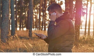 man in earphones is having rest and listening to music during listening to music on headphones on a smartphone running outdoors near modern private lifestyle houses. man running in the nature sports