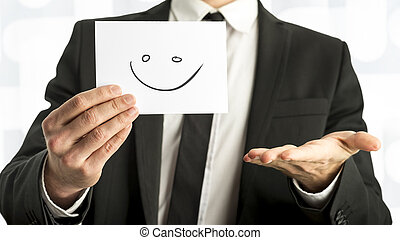 Man in elegant business suit holding up a white card with smiley face on it