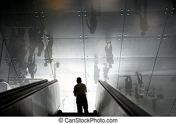 Man in escalators - Silhouette of a man going up escators,...