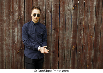 Man in fashion sunglasses with a blue shirt and black pants near a vintage wooden wall