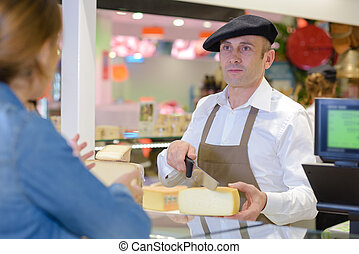 Man in French traditional dress serving cheese