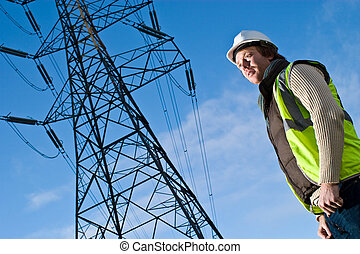 Man in front of an electricity pylon