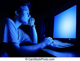 Man in front of computer screen. Dark night room and blue ...