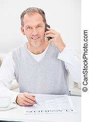 Man In Front Of Newspaper Talking On Cellphone