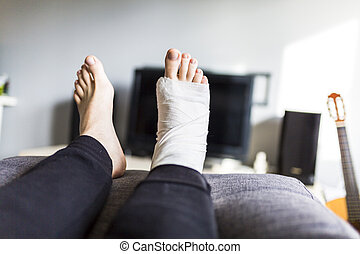 man in front of the TV with a broken leg