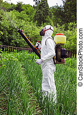 Man in full protective clothing spraying chemicals in the...