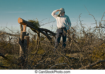 Man in gas mask among cut trees - Man in gas mask standing...